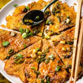 Sliced kimchi jeon drizzled with pancake sauce served on a big round plate