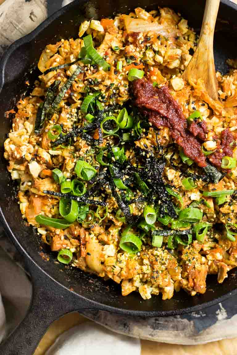 A cast iron skillet loaded with cauliflower fried rice, kimchi, and homemade gochujang sauce.