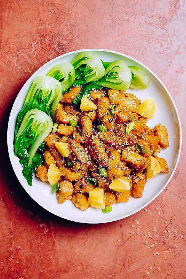 Baked Chinese-style orange chicken served with baby bok choy in a large white plate