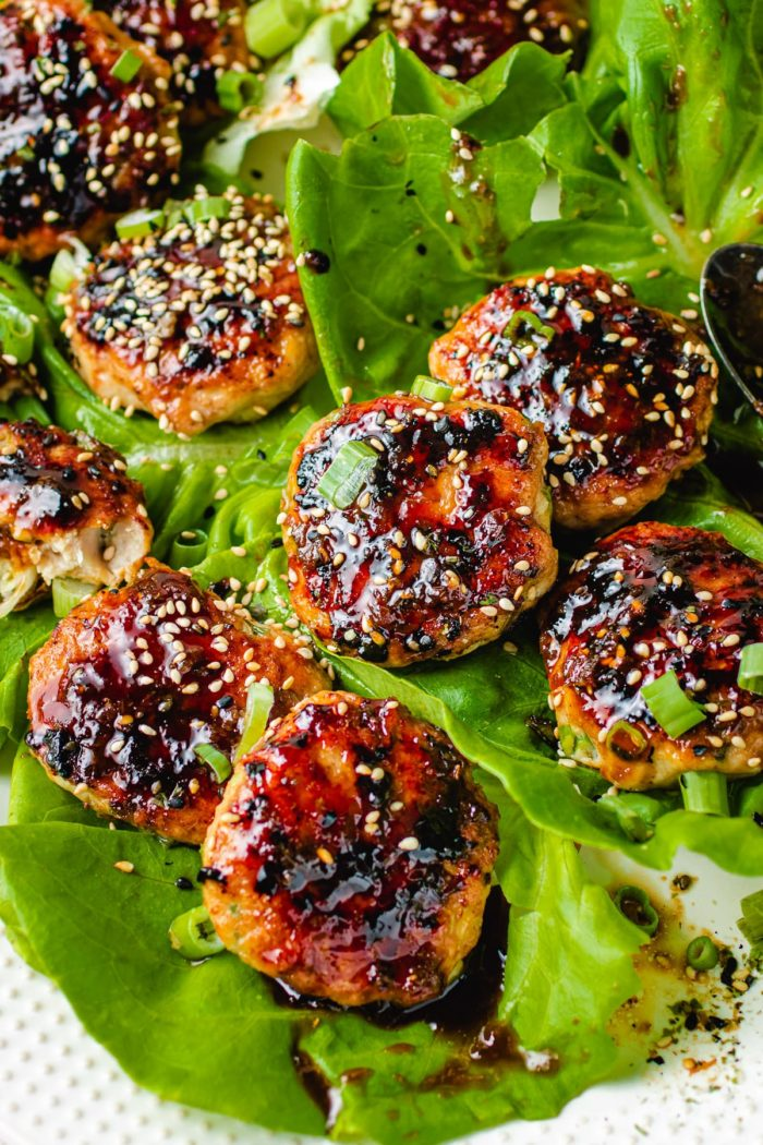 The picture shows displaying the grilled meatballs over a plate of butter lettuce