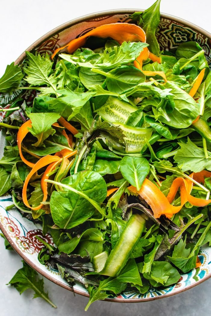 Photo shows a big bowl of fresh salad greens