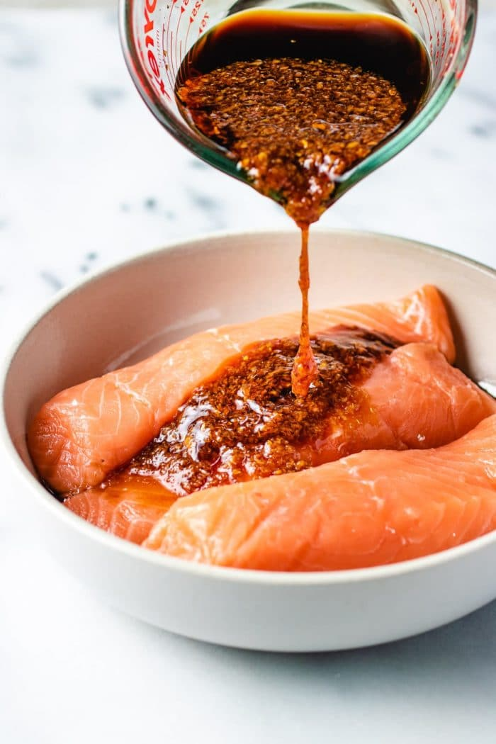 Photo shows pouring the salmon marinade over the fish fillets in plate