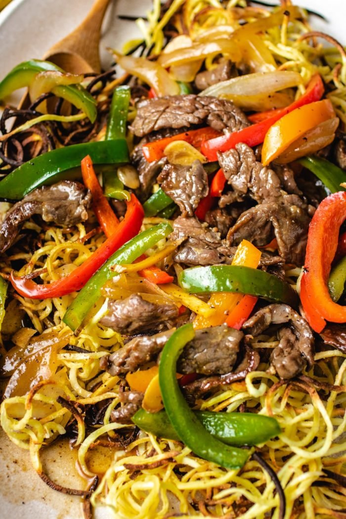 Another shot angle shows the crispy noodles with beef and peppers on a large plate