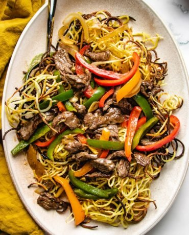 Cantonese beef chow mein feature images served on a large oval plate