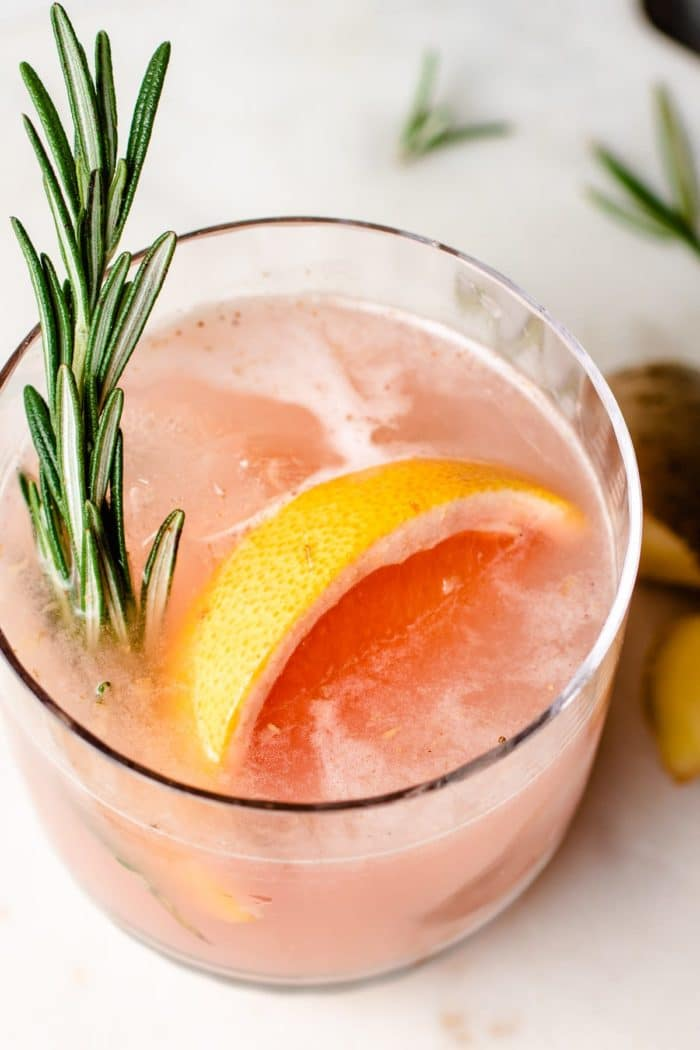 Adding rosemary and grapefruit slice to sake cocktail