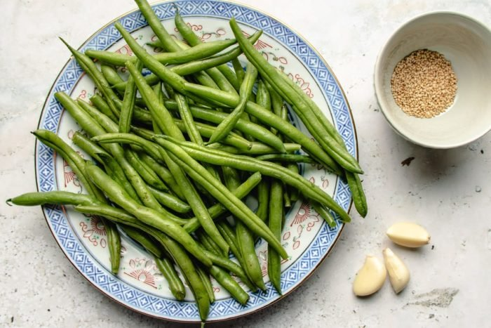 Ingredients with green beans, garlic, and sesame