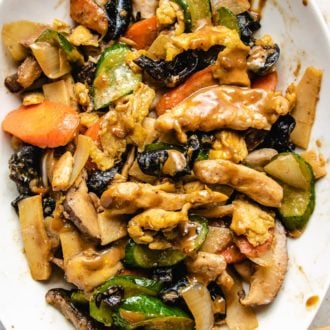 Moo Shu Chicken stir-fry with vegetables and sauce on a big white plate