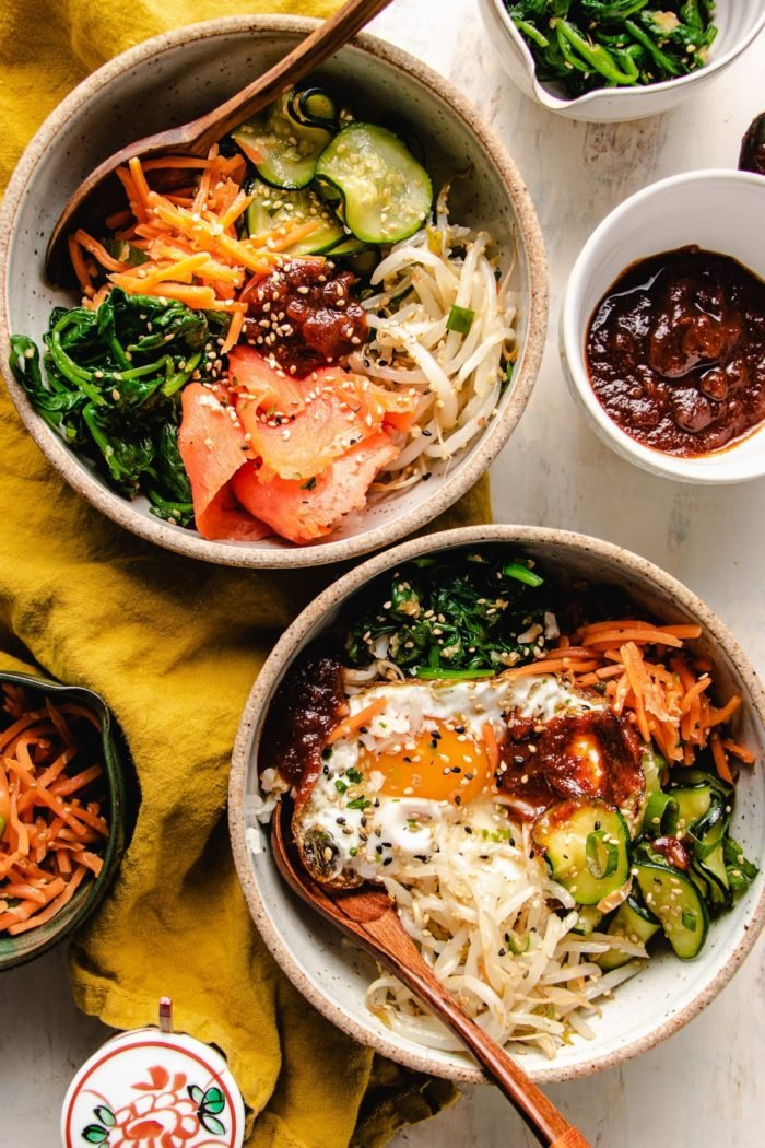 Vegetarian bibimbap recipe served in two individual bowls with the sauce on the side