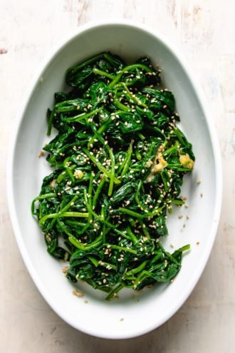 cooked and seasoned spinach in a white oval plate