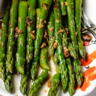 Easy Sauteed Asparagus with miso butter sauce served in a white plate