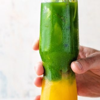 A tall glass filled with Ice, mango juice, and matcha tea