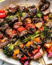 Grilled beef and vegetable kabobs on a big white plate