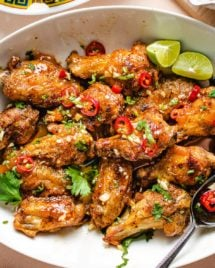 Air fried crispy chicken wings drizzled with sauce on a white plate