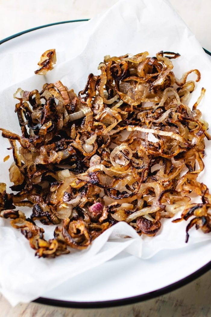 crispy fried shallots dry out on top of a parchment paper