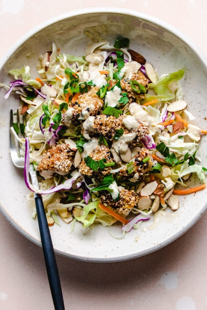 A photo shows crunch salad with dressing and air fried sesame chicken on top