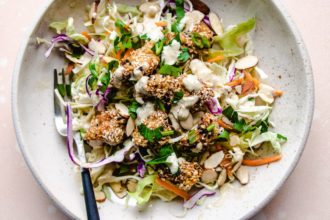 Sesame Chicken with coleslaw salads in a white plate
