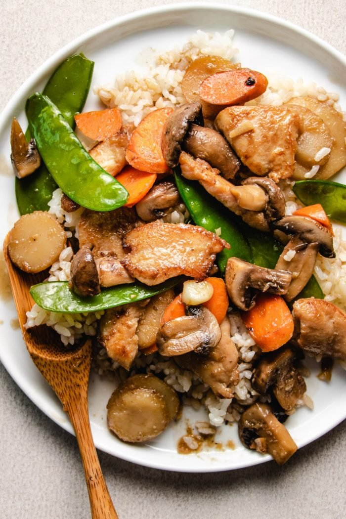 A close shot shows serving the cooked moo goo gai pan recipe with white rice on a white plate
