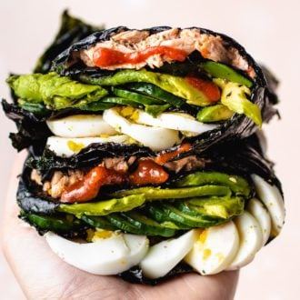 Photo shows one hand holding the stacks of food wrapped in nori sheets