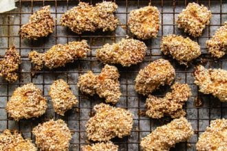 Chicken cubes coated with sesame seeds over a wire rack sheet pan