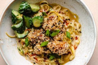 Sesame Chicken with zucchini noodles and cucumbers and sauce in a bowl