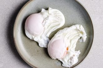 two poached eggs over a light gray dish