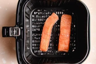 Photo shows two pieces of salmon in an air fryer basket with skin side down
