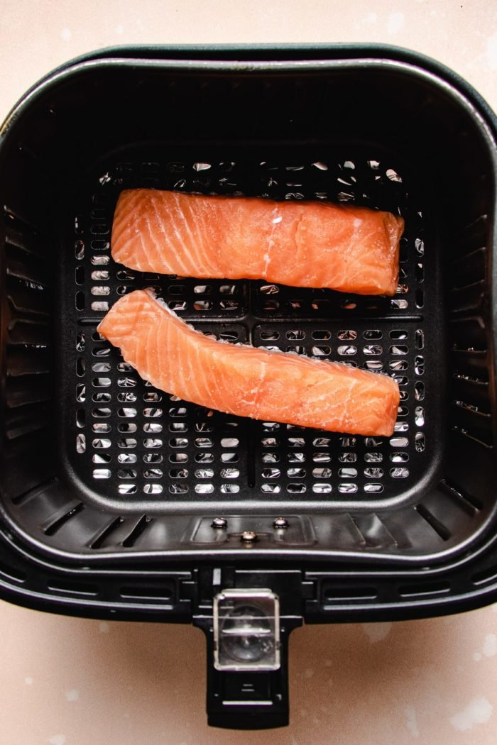 Photo shows two salmon fillets in air fryer basket with skin side down