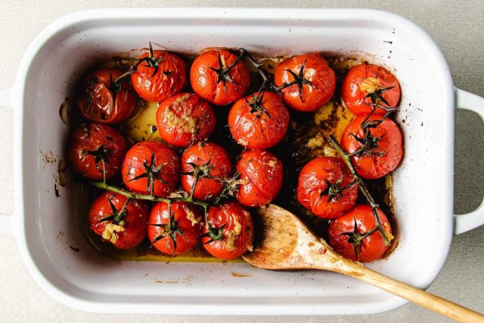 Roasted cherry tomatoes in a white casserole dish