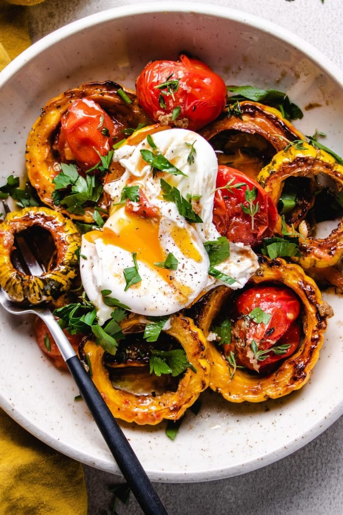 A feature photo shows roasted delicata squash with tomatoes and a poached egg on top over a white plate
