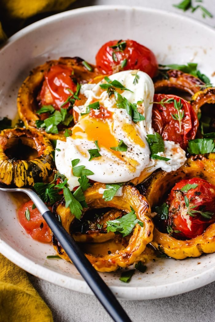 A close shot of the photo shows roasted squash with tomatoes and a sliced open poached eggs over a plate