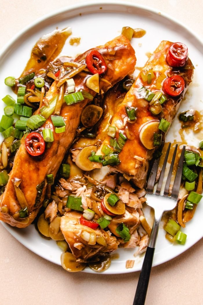 Two pieces of salmon fillets glazed in ginger sauce on a white plate