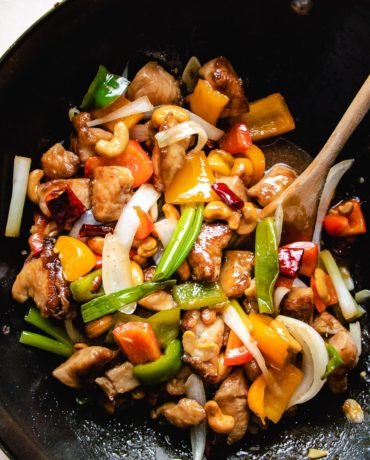 Photo shows stir fried chicken and cashew nuts with sauce in a big wok