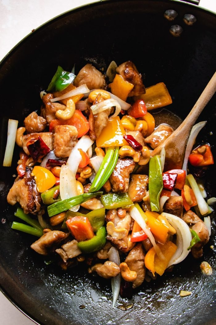Photo shows stir fried chicken and  nuts and sauce in a big wok