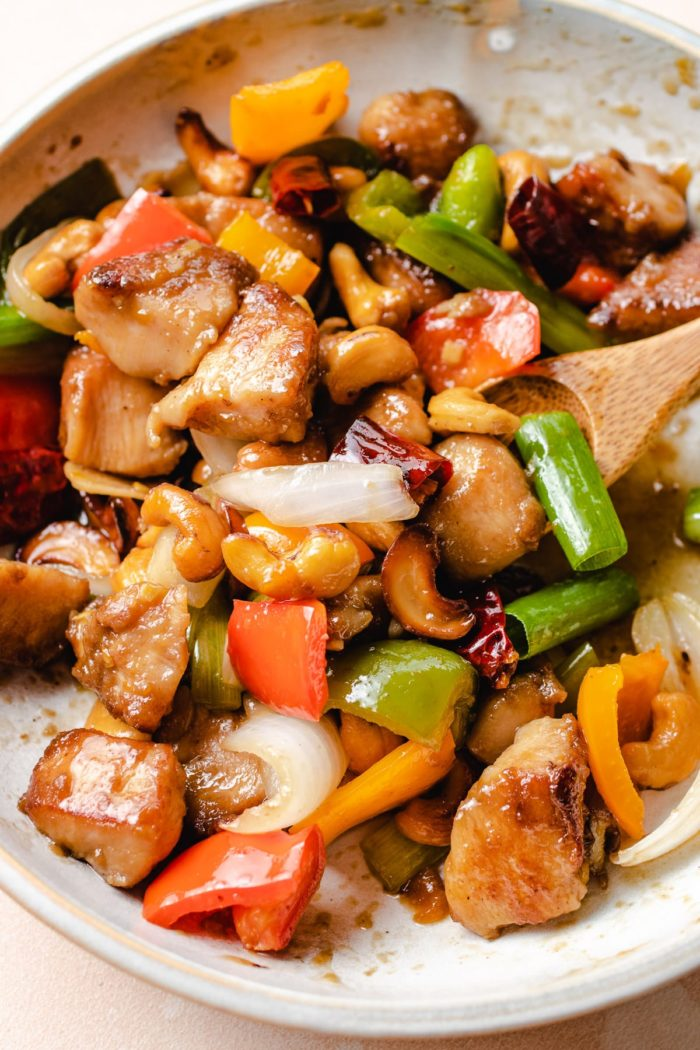 Thai style cashew chicken served on a white plate with a spoon