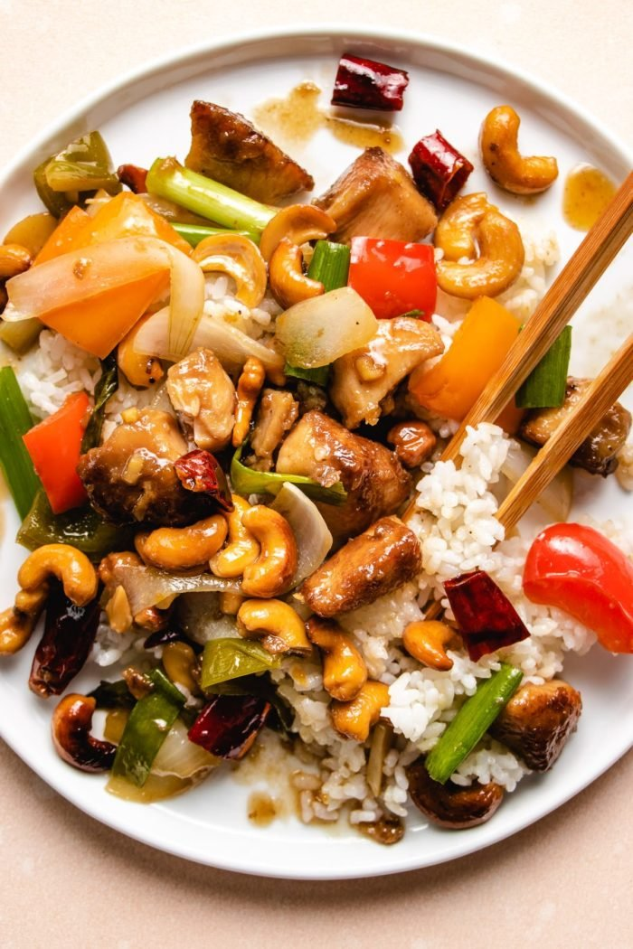 Photo shows serve the stir-fried chicken with cashew nuts over rice on a white plate