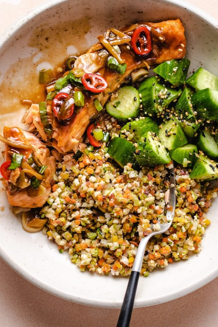Soy ginger glazed salmon fillets with cauli rice and cucumbers in a white bowl