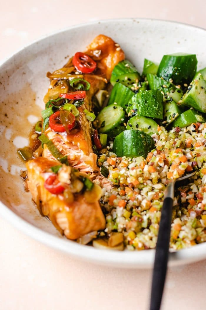 glaze soy ginger salmon served with cauliflower rice and cucumbers in a white bowl with a fork
